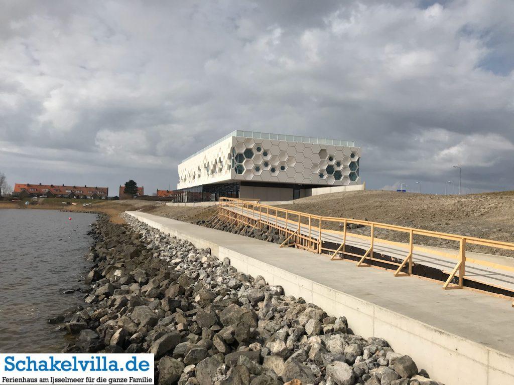 Blick von der Anlegestelle am IJsselmeer auf das Wadden Center am Abschlussdeich - Schakelvilla Ferienhaus für Familien am IJsselmeer in Makkum
